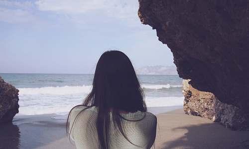 human woman sitting under rock facing sea person