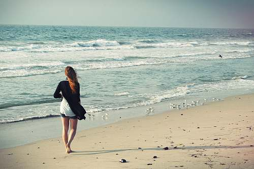 person woman standing at seashore beach