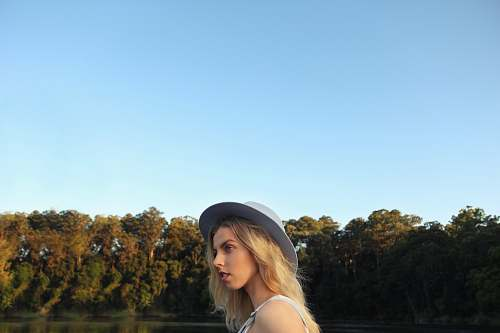 person woman standing near body of water and trees human