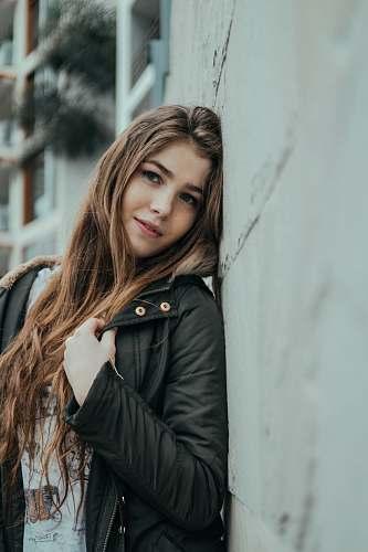 person woman standing near gray concrete wall human
