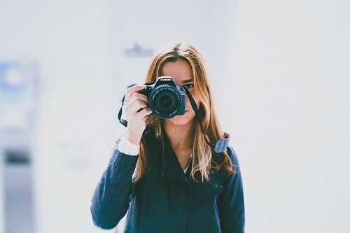 person woman taking photo using DSLR camera human