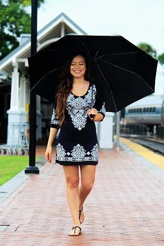 person woman walking on brown pathway while holding black umbrella human