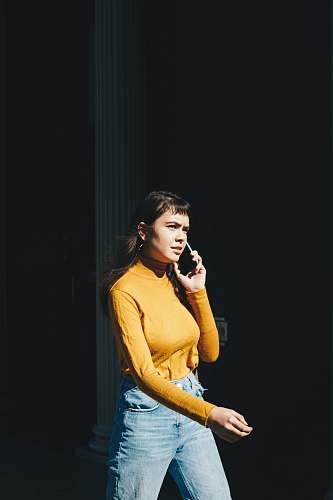 person woman walking with phone on her right ear during daytime human