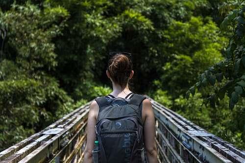 person woman wearing backpack walking on bridge human