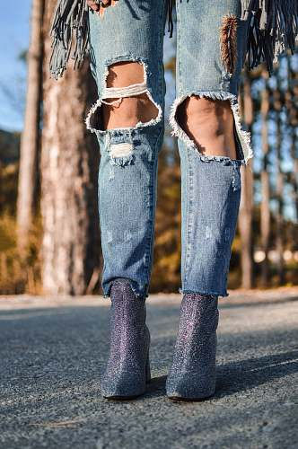 human woman wearing distressed blue denim jeans and pair of purple glitter booties jeans