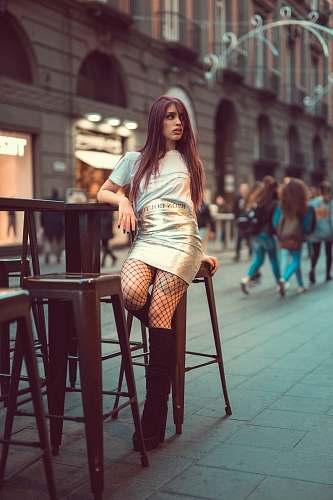 person woman wearing grey shirt and grey skirt sitting on stool beside people walking on pathway during daytime human