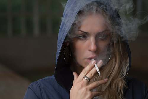 person woman wearing hoodie while holding cigarette human