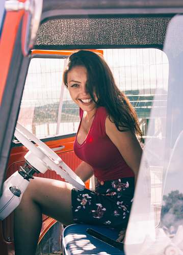 person woman wearing red tank top and multicolored floral skirt while sitting inside vehicle human