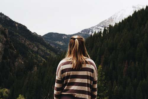 person woman wearing striped long-sleeved shirt facing mountains human