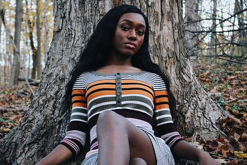 person woman wearing striped shirt laying near tree human