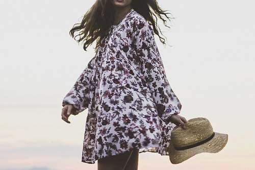 human woman wearing white and brown floral long-sleeved shirt while holding brown fedora hat person