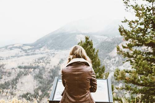woman back photo of woman wearing black leather jacket in front of snowed mountain female