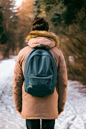 people back photo of woman wearing brown parka hoodie and green backpack on snow human