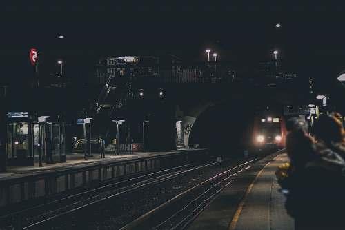 people black train under foot bridge human
