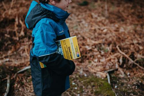 people boy carrying book standing on ground during daytime human