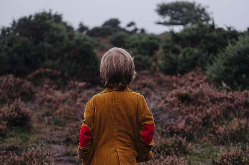 people boy wearing brown coat looking on trees in shallow focus photography human