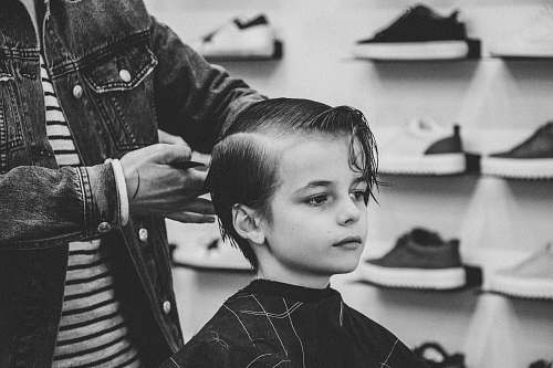 people greyscale photo of boy having a haircut black-and-white