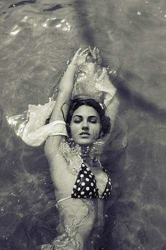 human greyscale photography of woman swimming people