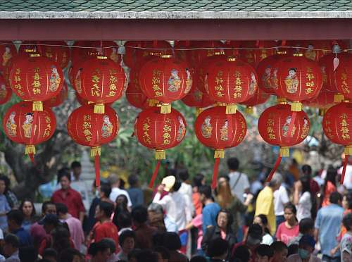people hanging round red lanterns near crowd at daytime lantern