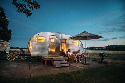 people man and woman sitting in front of RV trailer human