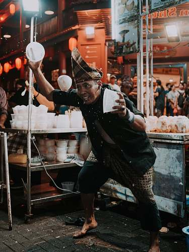 people man holding two white plastic bowls near food stall human