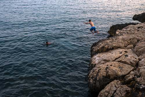 people man jumping on cliff human