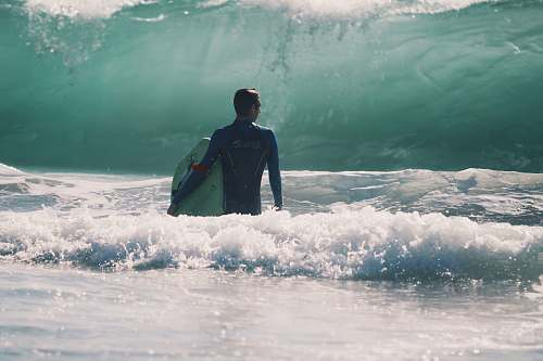 human man standing in body of water holding surfboard people