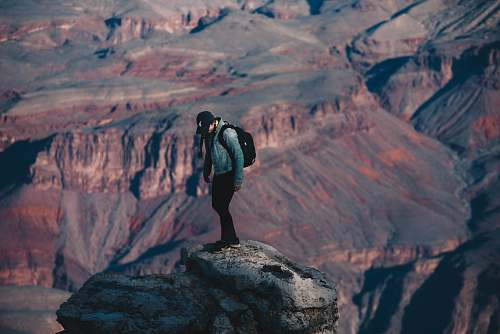 people man standing on rock cliff overlooking canyon during daytime nature