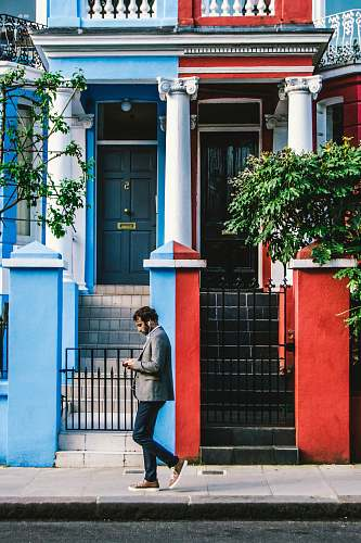 people man using smartphone passing by blue and red houses human