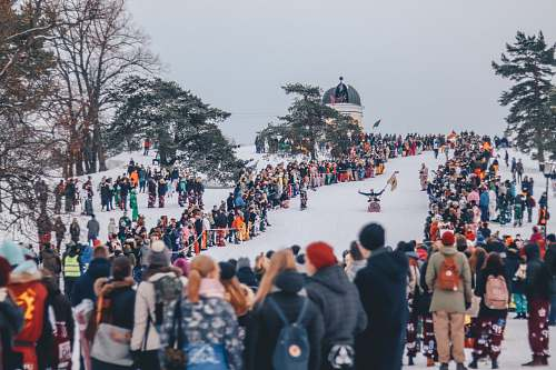 people people stands on snow and watches sled race during daytime crowd
