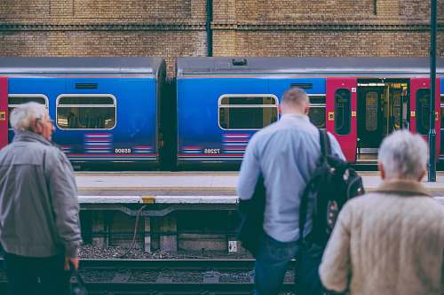 people person in gray dress shirt standing in front of train rail human