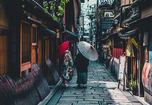 japan person walking on street while holding umbrella umbrella