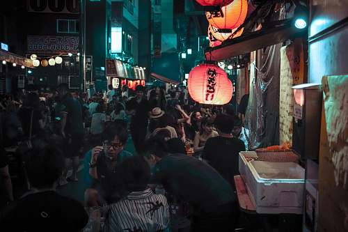 human photo of people gathering in market during nighttime people