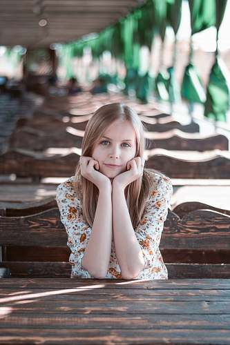 people selective focus of woman resting hands on face while sitting girl