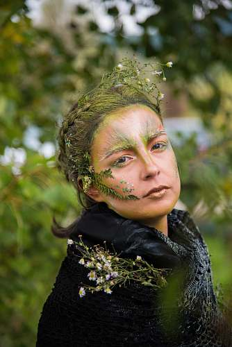 human selective focus photo of woman with nature-themed makeup people
