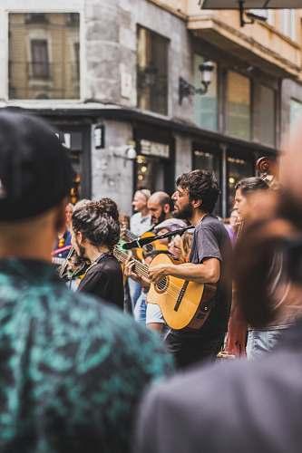 people tilt shift photography of man playing guitar human