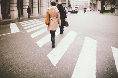 human two people walking on pedestrian lane towards gray concrete pillars during daytime photo people