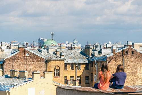 human two women sitting on roof overlooking building during daytime people