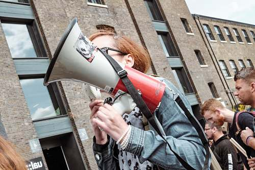 people woman holding red and white megaphone standing near building human