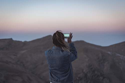 human woman in blue denim jacket taking picture of mountain people
