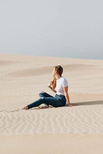 people woman sitting on desert at daytime human