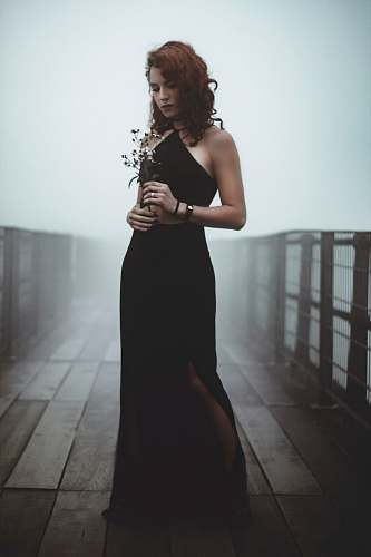 human woman standing in the bridge while holding flowers people