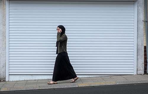 people woman walking beside closed roll-up door human