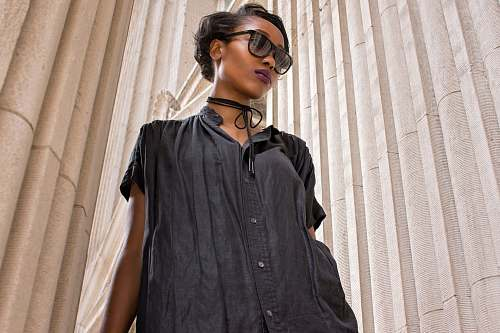 people woman wearing black short-sleeved dress near wall human