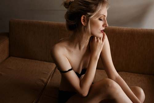 photo people woman wearing black underwear sitting on brown couch human free for commercial use images