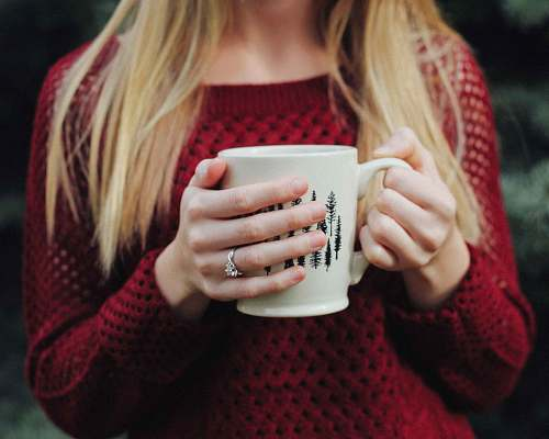 people woman wearing red sweater holding white and black ceramic mug human