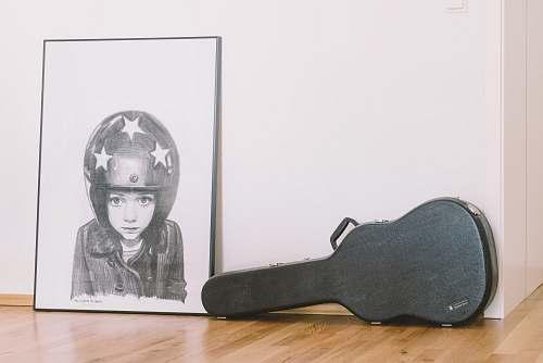clothing black guitar case beside white wall helmet