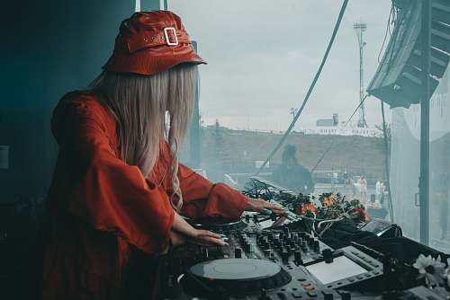 clothing female DJ in red blouse using black DJ software controller during daytime hat
