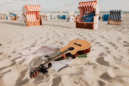 guitar brown acoustic guitar on sand during day time nature