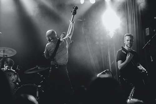person grayscale photo of band playing on stage people